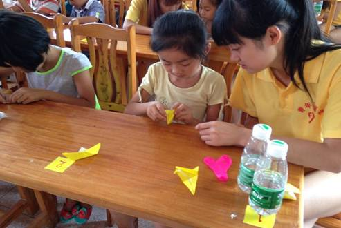 志愿者辅导小朋友折纸鹤